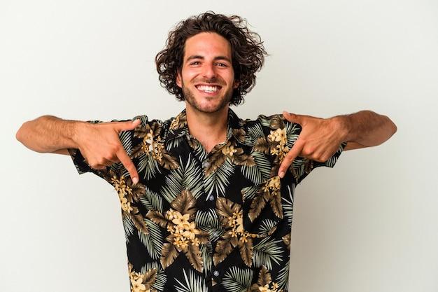Młody kaukaski mężczyzna na białym tle wskazuje palcami w dół, pozytywne uczucie.