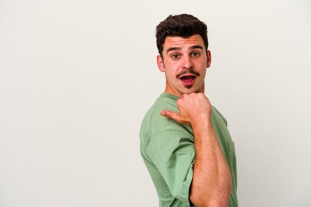 Młody kaukaski mężczyzna na białym tle wskazuje palcem kciuka, śmiejąc się i beztrosko.