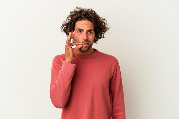 Młody kaukaski mężczyzna na białym tle z palcami na ustach zachowując tajemnicę.