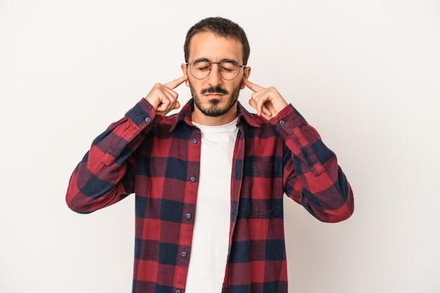 Młody kaukaski mężczyzna na białym tle zakrywający uszy palcami, zestresowany i zdesperowany głośnym otoczeniem.
