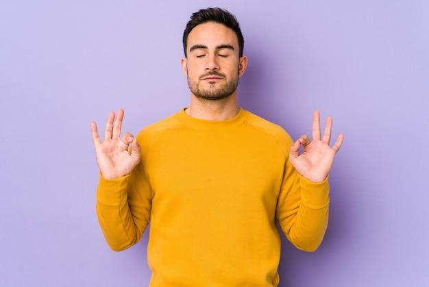 Młody kaukaski mężczyzna na fioletowe ściany relaksuje po ciężkim dniu pracy, wykonując jogi.