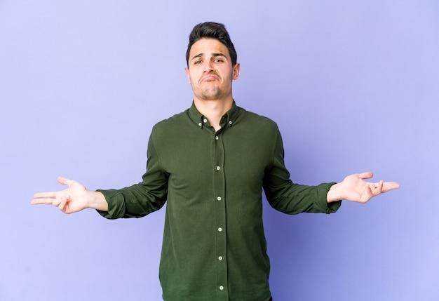 Młody kaukaski mężczyzna na fioletowej ścianie wątpi i wzrusza ramionami w pytającym geście.