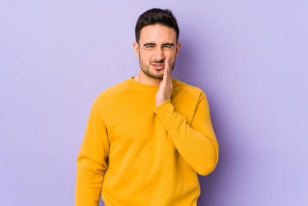 Młody kaukaski mężczyzna na fioletowym tle o silnym bólu zębów, bólach trzonowych.