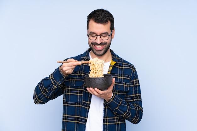 Młody kaukaski mężczyzna na niebieską ścianą trzyma miskę makaronu z pałeczkami