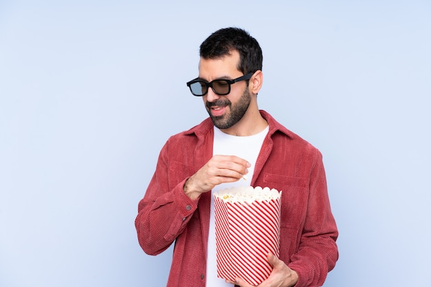 Młody kaukaski mężczyzna na niebieską ścianą w okularach 3d i posiadający duże wiadro popcorns
