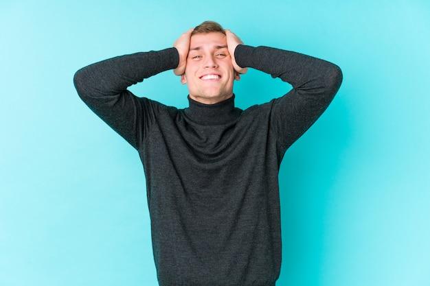 Młody kaukaski mężczyzna na niebieskiej ścianie śmieje się radośnie trzymając ręce na głowie. koncepcja szczęścia.