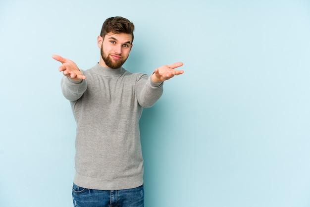 Młody kaukaski mężczyzna na niebieskiej ścianie sprawia, że skala z rękami, czuje się szczęśliwy i pewny siebie.