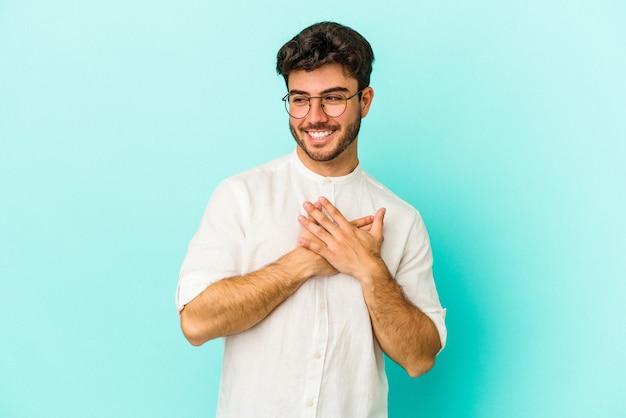 Młody kaukaski mężczyzna na niebieskim tle ma przyjazny wyraz, przyciskając dłoń do klatki piersiowej. koncepcja miłości.