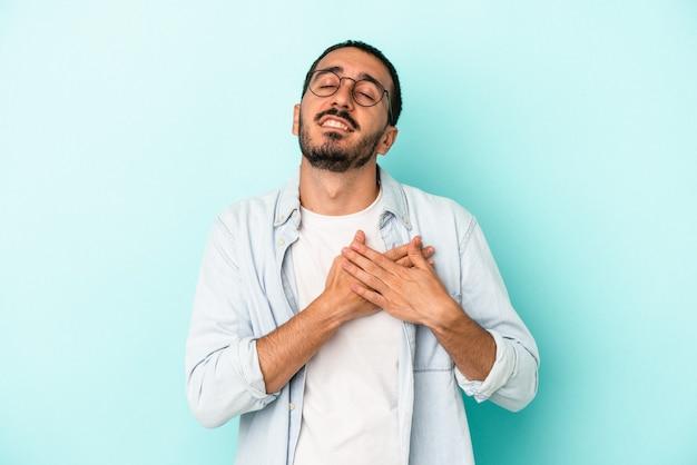 Młody kaukaski mężczyzna na niebieskim tle ma przyjazny wyraz twarzy, przyciskając dłoń do klatki piersiowej. koncepcja miłości.