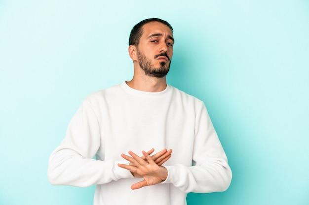 Młody kaukaski mężczyzna na niebieskim tle robi gest odmowy