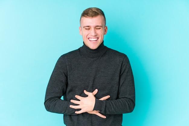 Młody kaukaski mężczyzna na niebieskim tle śmieje się radośnie i dobrze się trzyma na brzuchu.