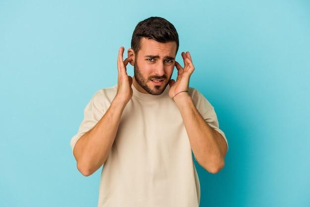 Młody kaukaski mężczyzna na niebieskim tle zakrywający uszy palcami, zestresowany i zdesperowany głośnym otoczeniem.