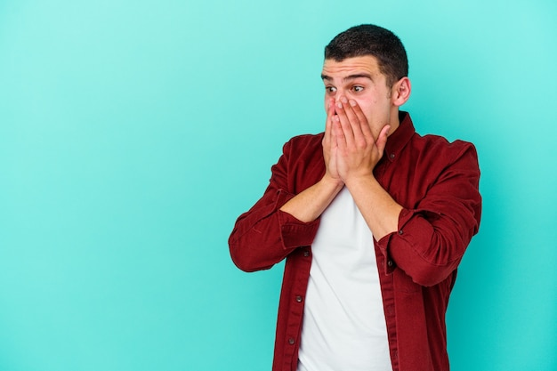 Młody kaukaski mężczyzna na niebiesko zamyślony patrząc na przestrzeń kopii obejmującej usta ręką.