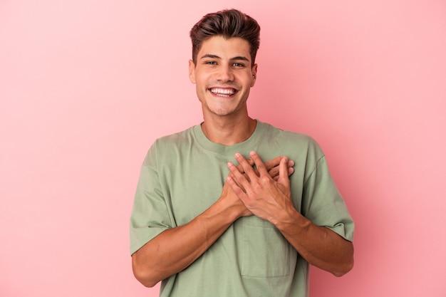 Młody kaukaski mężczyzna na różowym tle ma przyjazny wyraz twarzy, przyciskając dłoń do klatki piersiowej. koncepcja miłości.