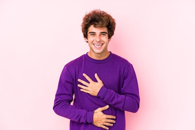 Młody kaukaski mężczyzna na różowym tle na białym tle śmieje się radośnie i dobrze się bawi trzymając ręce na brzuchu.