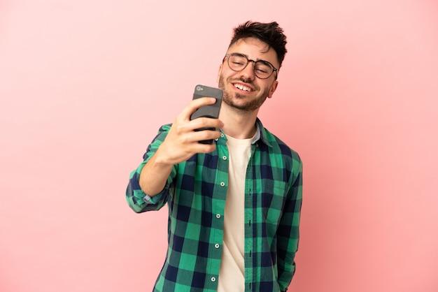 Młody kaukaski mężczyzna na różowym tle robi selfie