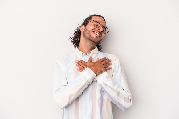 Młody kaukaski mężczyzna na szarym tle ma przyjazny wyraz, przyciskając dłoń do klatki piersiowej. koncepcja miłości.