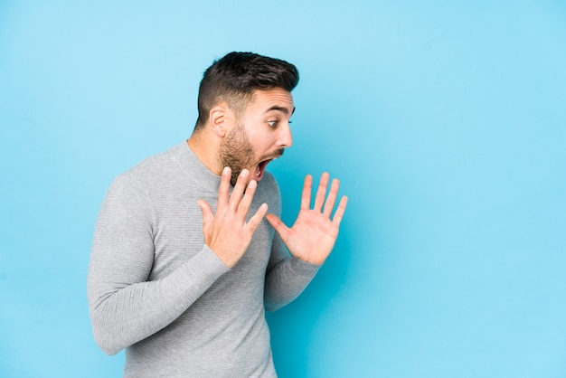 Młody kaukaski mężczyzna na tle niebieskiej ściany na białym tle krzyczy głośno, ma otwarte oczy i spięte ręce.