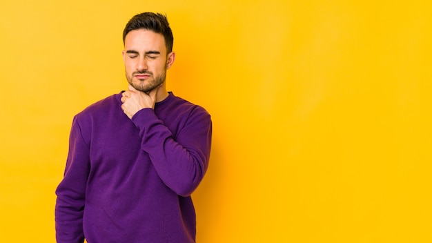 Młody kaukaski mężczyzna na żółtej ścianie cierpi na ból gardła z powodu wirusa lub infekcji.