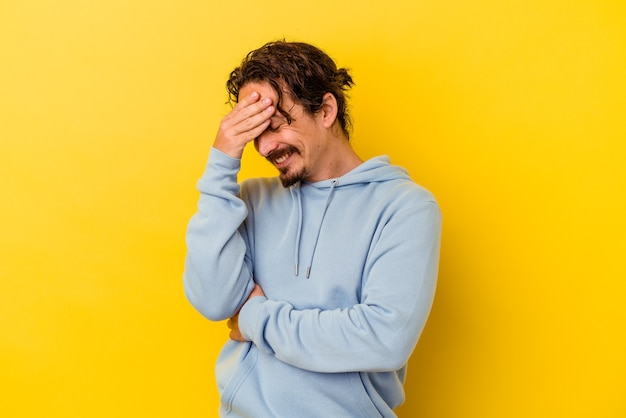 Młody kaukaski mężczyzna na żółtej ścianie mruga do przodu palcami, zawstydzona zakrywająca twarz