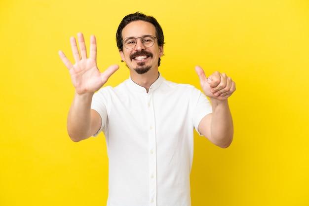 Młody kaukaski mężczyzna na żółtym tle liczący sześć palcami