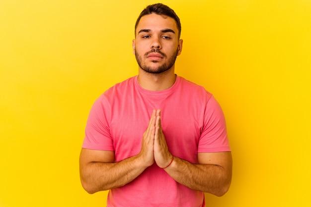 Młody kaukaski mężczyzna na żółtym tle modlący się, okazujący oddanie, osoba religijna szukająca boskiej inspiracji.
