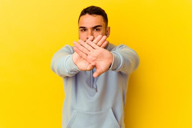 Młody kaukaski mężczyzna na żółtym tle robi gest odmowy