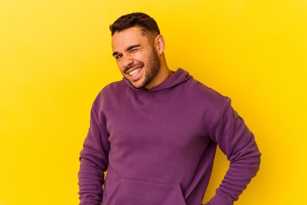 Młody kaukaski mężczyzna na żółtym tle śmieje się i zamyka oczy, czuje się zrelaksowany i szczęśliwy.
