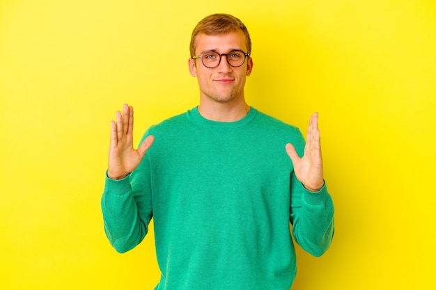 Młody kaukaski mężczyzna na żółtym tle, trzymając coś małego palcami wskazującymi, uśmiechnięty i pewny siebie.