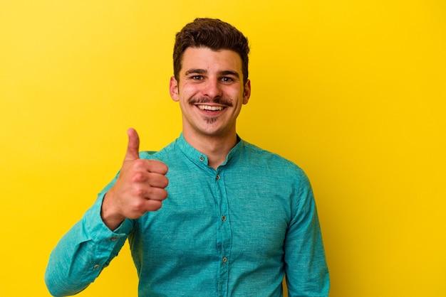 Młody kaukaski mężczyzna na żółtym tle uśmiecha się i podnosi kciuk w górę