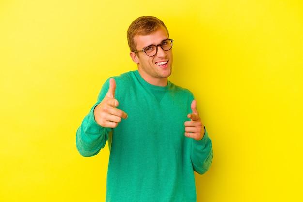Młody kaukaski mężczyzna na żółtym tle wskazując palcami do przodu.