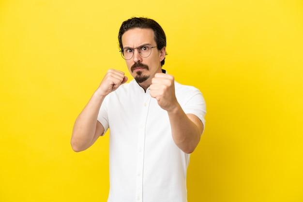 Młody kaukaski mężczyzna na żółtym tle z gestem walki