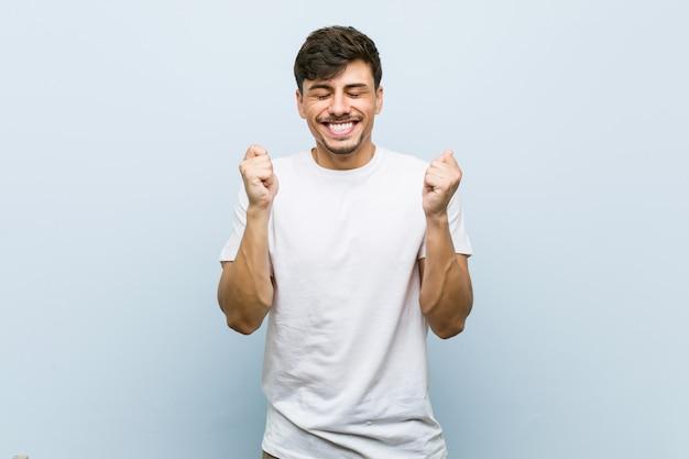 Młody kaukaski mężczyzna nosi biały tshirt podnosząc pięść, czując się szczęśliwy i udany. zwycięstwo .