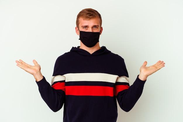 Młody kaukaski mężczyzna noszący maskę na wirusa na białym tle sprawia, że skala z rękami, czuje się szczęśliwa i pewna siebie.