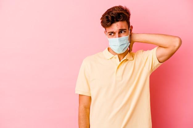 Młody kaukaski mężczyzna noszący ochronę przed koronawirusem na białym tle na różowym tle dotyka tyłu głowy, myśląc i dokonując wyboru.