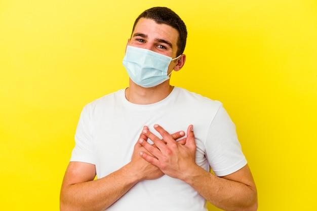 Młody kaukaski mężczyzna noszący ochronę przed koronawirusem wyizolowaną na żółto ma przyjazny wyraz twarzy, przyciskając dłoń do klatki piersiowej. koncepcja miłości.