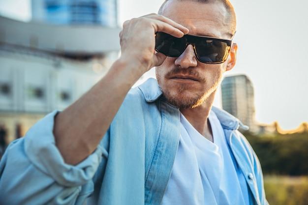 Młody kaukaski mężczyzna noszenie okularów przeciwsłonecznych, nowoczesny strzał w efekt ziarna filmu i styl vintage. zachód słońca w letni wieczór. ulica miasta. stonowany w kolorze morskiej pomarańczy. wygląda pewnie i fajnie.