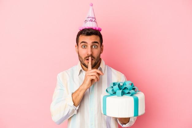 Młody kaukaski mężczyzna obchodzi swoje urodziny na białym tle na różowym tle, zachowując tajemnicę lub prosząc o ciszę.