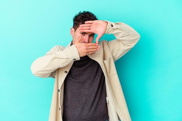 Młody kaukaski mężczyzna odizolowany na niebieskiej ścianie mruga do przodu palcami, zawstydzona zakrywająca twarz