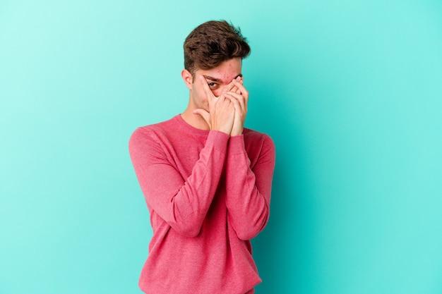 Młody kaukaski mężczyzna odizolowany na niebieskiej ścianie mruga przez palce przestraszony i zdenerwowany
