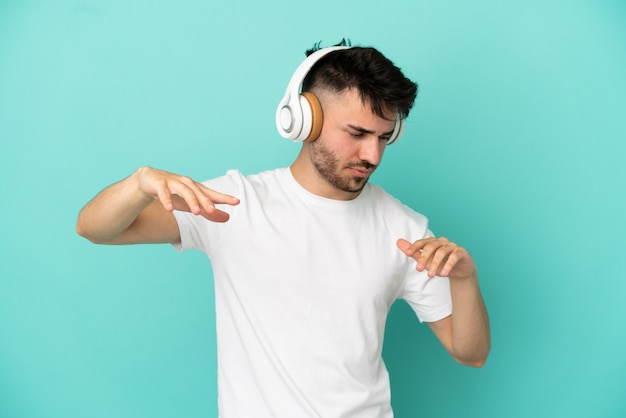 Młody kaukaski mężczyzna odizolowany na niebieskim tle, słuchając muzyki i tańcząc