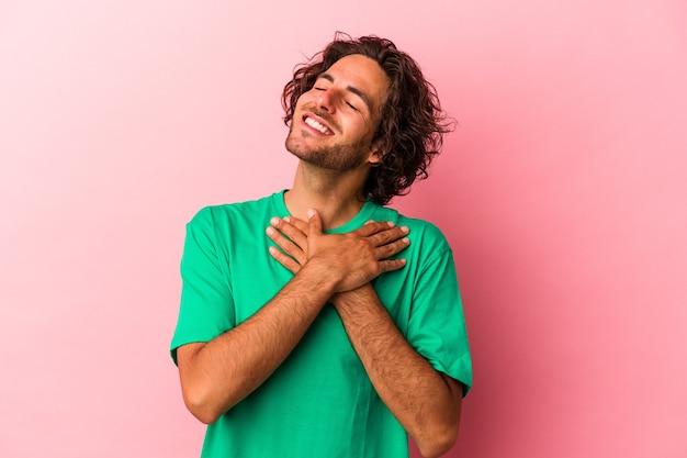 Młody kaukaski mężczyzna odizolowany na różowym bakcground ma przyjazny wyraz twarzy, przyciskając dłoń do klatki piersiowej. koncepcja miłości.