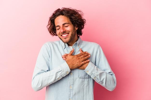 Młody kaukaski mężczyzna odizolowany na różowym tle ma przyjazny wyraz twarzy, przyciskając dłoń do klatki piersiowej. koncepcja miłości.
