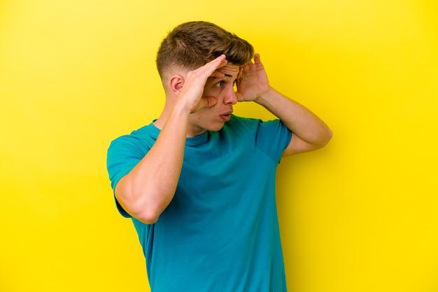 Młody kaukaski mężczyzna odizolowany na żółtej ścianie, mając oczy otwarte, aby znaleźć okazję do sukcesu.