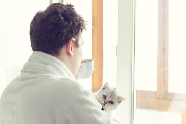 Młody kaukaski mężczyzna pije kawę w pobliżu okna. trzyma kota. wcześnie rano słońce.
