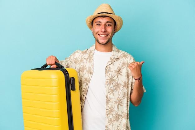 Młody kaukaski mężczyzna podróżujący na białym tle na niebieskim tle uśmiechający się i unoszący kciuk w górę
