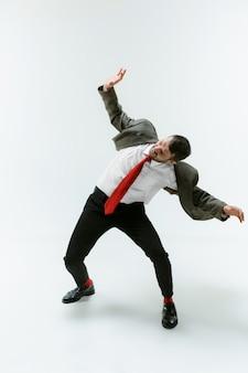 Młody kaukaski mężczyzna porusza się elastyczny na białej ścianie