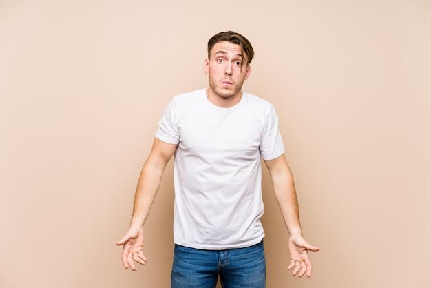 Młody kaukaski mężczyzna pozowanie na białym tle wzrusza ramionami i jest zdezorientowany.