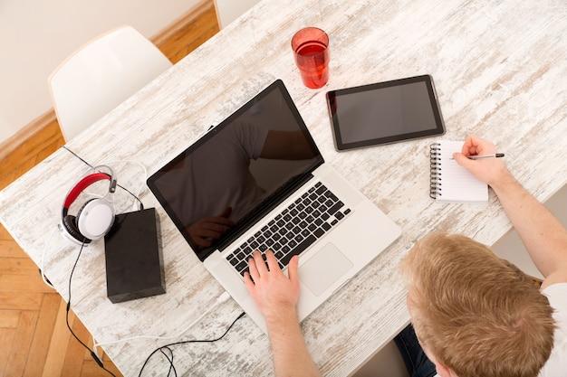 Młody kaukaski mężczyzna pracujący w swoim domowym biurze, widziany z góry.