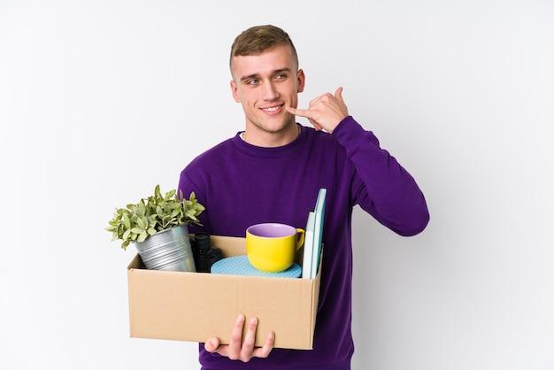 Młody kaukaski mężczyzna przenosi się do nowego domu, pokazując gest połączenia telefonu komórkowego z palcami.